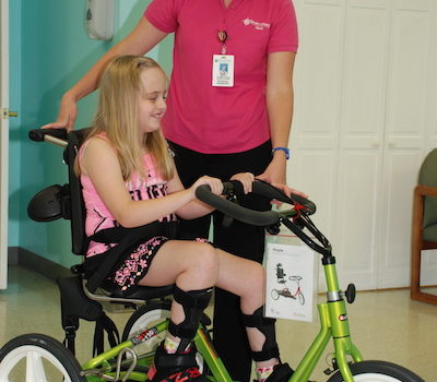 therapy smiles as child rides therapy bike