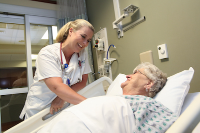 Nurse smiling at patient in bed