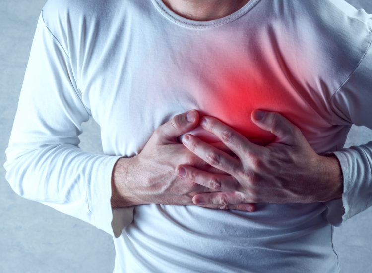 Man clutching chest in pain having a heart attack.