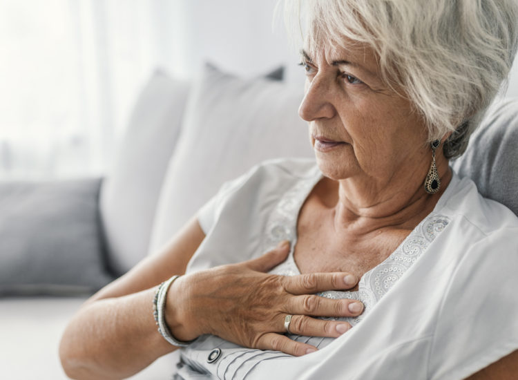 Woman clutching chest in pain.