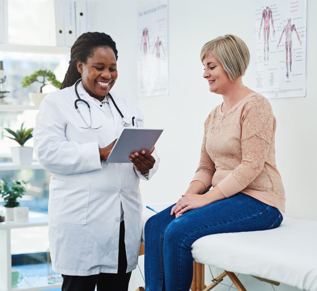 African American female doctor addressing caucasian woman medical needs.